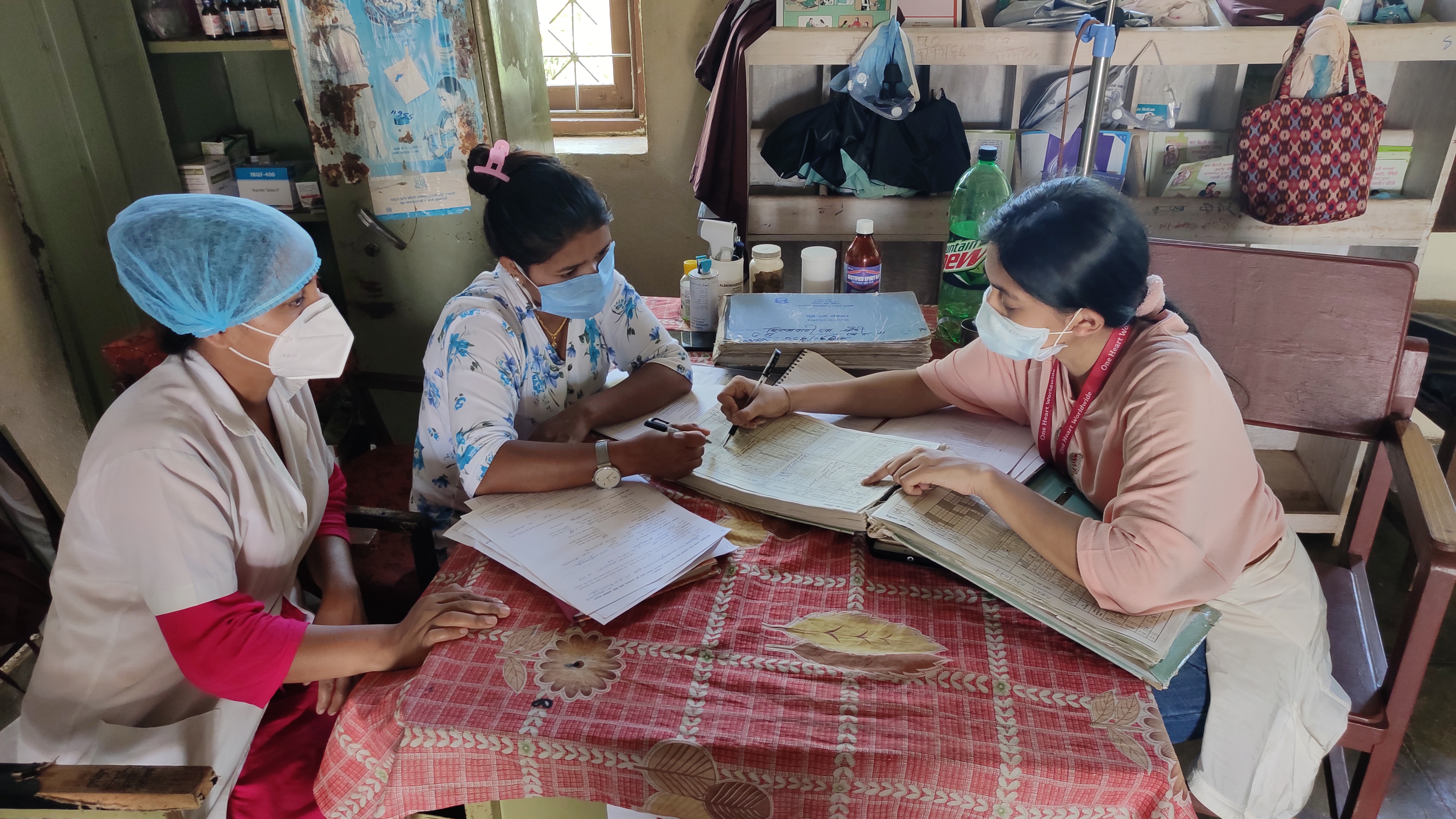 Credit: One Heart Worldwide. Description: Photo of three women sitting at a table for nursing staff training. One women is pointing to a book and the other two are looking at what she's pointing out.