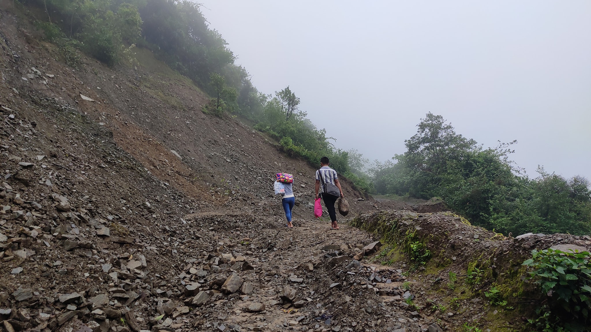 Credit: One Heart Worldwide. Description: Photo shows two people walking barefoot on rugged terrain. Between the two of them, they are carrying five bags.