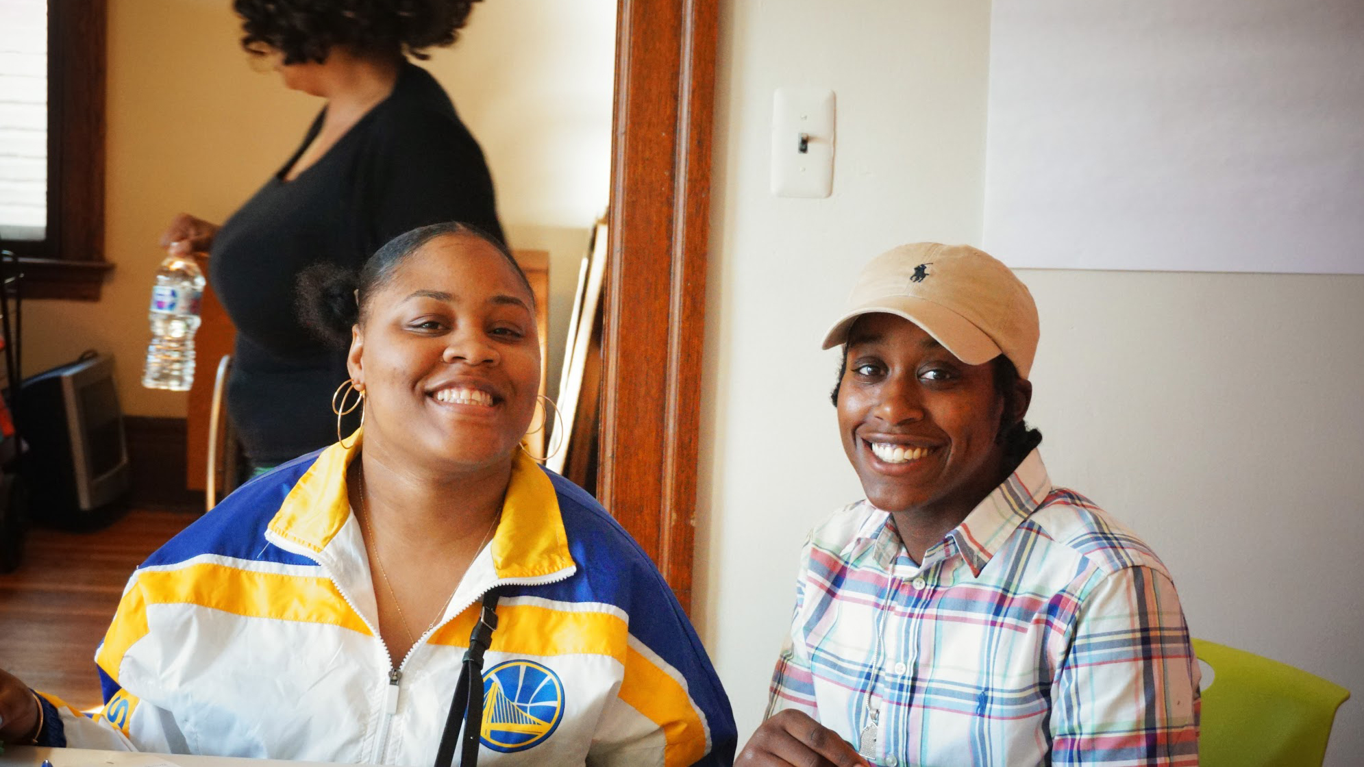 Photo shows two people sitting at a table. The one on the left is wearing a yellow, white and blue windbreaker. The one on the right is wearing a plaid shirt and a tan hat. Both are smiling.